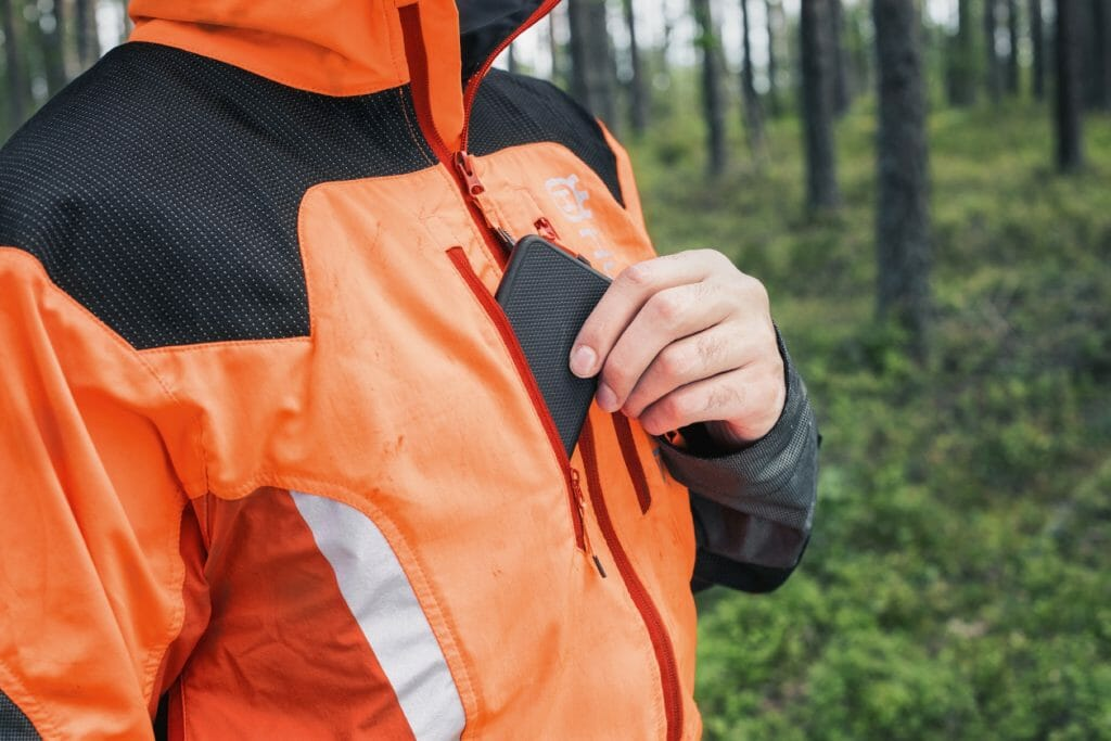 A mobile phone is taken out from a chest pocket of a forestry jacket