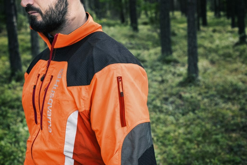 Forestry worker wearing a signal coloured forestry jacket with reflective fields