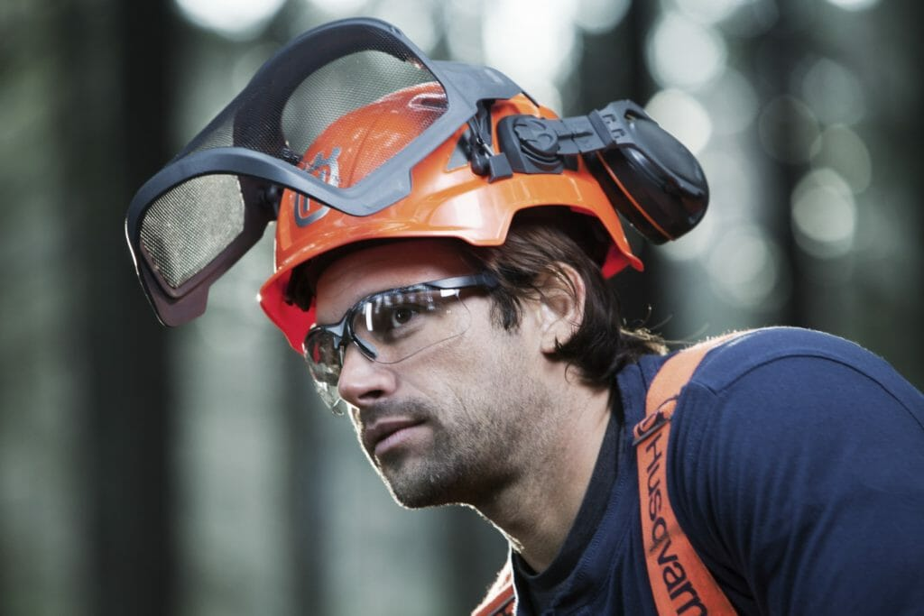 Close-up of forestry worker with protective glasses and a helmet with earmuffs and folded up visors