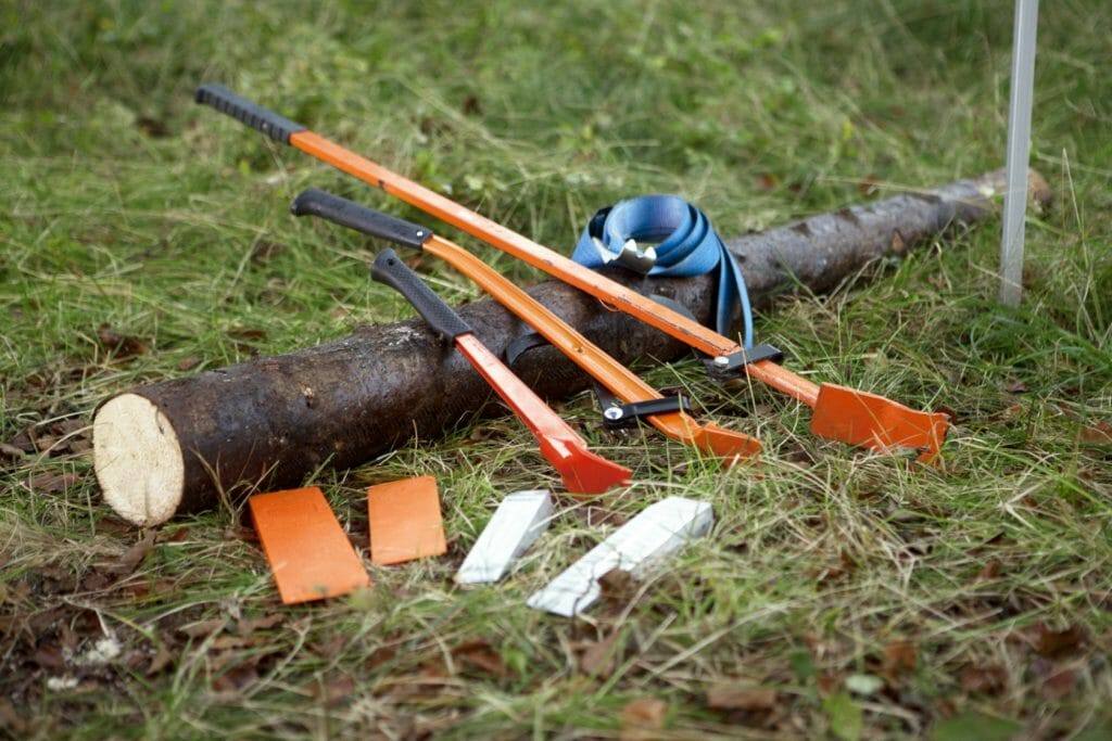 Breaking bars, wedges and a turning strap lying on a small log on the ground