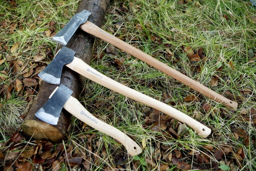 Tree axes in different sizes with wooden handles lying on a log on the ground