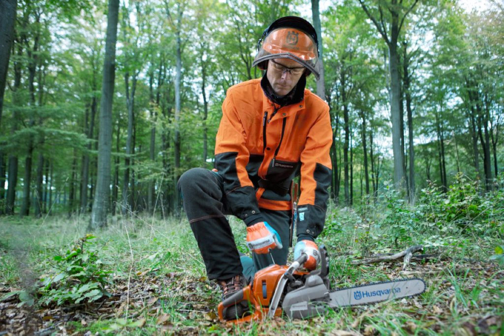 Forestry worker starting a chainsaw between his legs